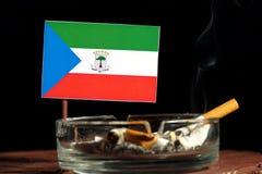 Drapeau de la Guinée équatoriale avec la cigarette brûlante dans le cendrier d'isolement sur le noir Images stock