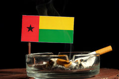 Drapeau de la Guinée-Bissau avec la cigarette brûlante dans le cendrier sur le noir Photos libres de droits