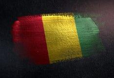 Drapeau de la Guinée fait de peinture métallique de brosse sur le mur foncé grunge illustration stock