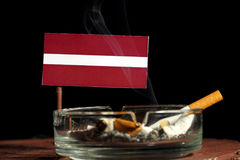 Drapeau de la Lettonie avec la cigarette brûlante dans le cendrier sur le noir Images libres de droits