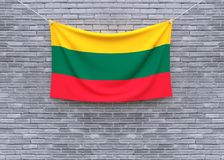 Drapeau de la Lithuanie accrochant sur le mur de briques photo stock