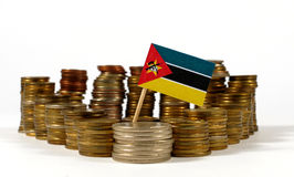 Drapeau de la Mozambique avec la pile de pièces de monnaie d'argent Photographie stock