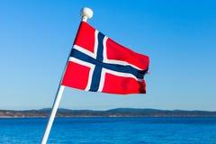 Drapeau de la Norvège au-dessus de la mer et du ciel bleu Photographie stock libre de droits