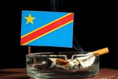 Drapeau de la République démocratique du Congo avec la cigarette brûlante dans le cendrier d'isolement sur le noir Photo libre de droits