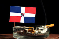 Drapeau de la République Dominicaine avec la cigarette brûlante dans le cendrier d'isolement sur le noir Photo stock