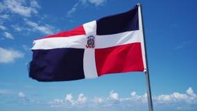 Drapeau de la République Dominicaine ondulant contre le ciel bleu avec des nuages banque de vidéos