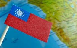 Drapeau de Myanmar avec une carte de globe comme fond Images stock