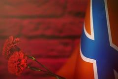 Drapeau de Novorossiya pour l'honneur du jour ou du Jour du Souvenir de vétérans avec la maquette rouge de deux fleurs d'oeillet  illustration de vecteur