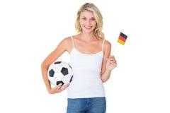 Drapeau de ondulation assez allemand de passioné du football tenant la boule Photographie stock libre de droits