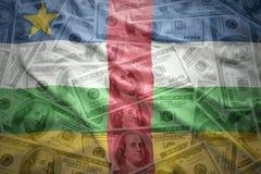 Drapeau de ondulation coloré de la république centrafricaine sur un fond d'argent du dollar Photographie stock libre de droits