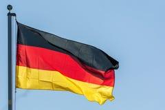 Drapeau de ondulation de la république Fédérale d'Allemagne devant le ciel bleu photographie stock