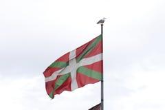Drapeau de pays Basque, avec une mouette sur le poteau Photos stock