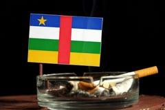 Drapeau de République Centrafricaine avec la cigarette brûlante dans le cendrier d'isolement sur le noir Photo libre de droits