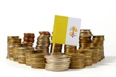 Drapeau de Ville du Vatican avec la pile de pièces de monnaie d'argent Image libre de droits