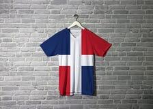 Drapeau dominicain sur la chemise et accrocher sur le mur avec le papier peint de modèle de brique images libres de droits