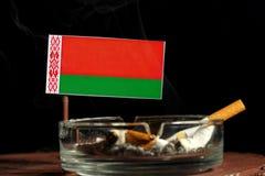 Drapeau du Belarus avec la cigarette brûlante dans le cendrier d'isolement sur le noir Photographie stock