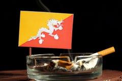 Drapeau du Bhutan avec la cigarette brûlante dans le cendrier d'isolement sur le noir Photographie stock libre de droits