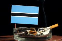 Drapeau du Botswana avec la cigarette brûlante dans le cendrier d'isolement sur le noir Image libre de droits
