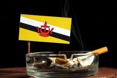 Drapeau du Brunei avec la cigarette brûlante dans le cendrier d'isolement sur le noir Photographie stock libre de droits