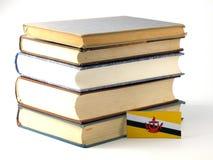 Drapeau du Brunei avec la pile des livres sur le fond blanc photos stock