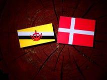 Drapeau du Brunei avec le drapeau danois sur un tronçon d'arbre d'isolement image libre de droits