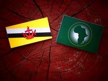 Drapeau du Brunei avec le drapeau des syndicats africains sur un tronçon d'arbre image libre de droits