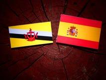 Drapeau du Brunei avec le drapeau espagnol sur un tronçon d'arbre photos libres de droits