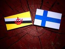 Drapeau du Brunei avec le drapeau finlandais sur un tronçon d'arbre d'isolement photographie stock
