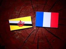 Drapeau du Brunei avec le drapeau français sur un tronçon d'arbre d'isolement photos stock