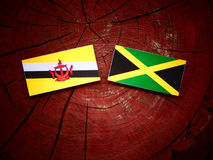 Drapeau du Brunei avec le drapeau jamaïcain sur un tronçon d'arbre photo stock