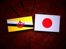 Drapeau du Brunei avec le drapeau japonais sur un tronçon d'arbre d'isolement image stock