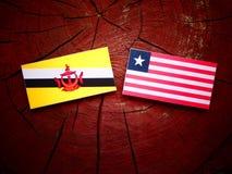 Drapeau du Brunei avec le drapeau libérien sur un tronçon d'arbre d'isolement image stock