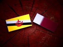 Drapeau du Brunei avec le drapeau qatari sur un tronçon d'arbre d'isolement image libre de droits