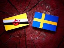 Drapeau du Brunei avec le drapeau suédois sur un tronçon d'arbre photographie stock libre de droits