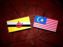 Drapeau du Brunei avec le drapeau malaisien sur un tronçon d'arbre d'isolement images stock