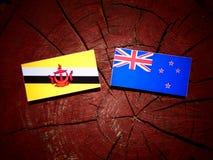 Drapeau du Brunei avec le drapeau du Nouvelle-Zélande sur un tronçon d'arbre d'isolement photo stock