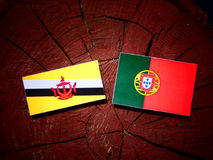 Drapeau du Brunei avec le drapeau portugais sur un tronçon d'arbre d'isolement photographie stock