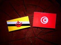 Drapeau du Brunei avec le drapeau tunisien sur un tronçon d'arbre d'isolement photographie stock