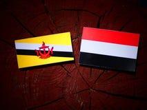 Drapeau du Brunei avec le drapeau yéménite sur un tronçon d'arbre d'isolement photos libres de droits