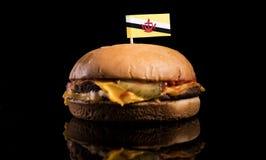 Drapeau du Brunei sur l'hamburger d'isolement sur le noir photo stock