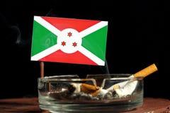 Drapeau du Burundi avec la cigarette brûlante dans le cendrier d'isolement sur le noir Images stock