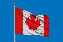 Drapeau du Canada ondulant dans le vent contre le ciel bleu profond Indicateur canadien illustration libre de droits