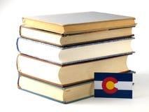 Drapeau du Colorado avec la pile des livres sur le fond blanc photographie stock
