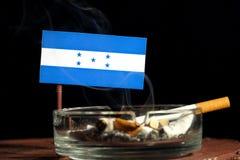 Drapeau du Honduras avec la cigarette brûlante dans le cendrier sur le noir Photographie stock