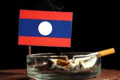 Drapeau du Laos avec la cigarette brûlante dans le cendrier sur le noir Photos stock