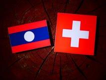 Drapeau du Laos avec le drapeau suisse sur un tronçon d'arbre Photo stock