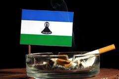 Drapeau du Lesotho avec la cigarette brûlante dans le cendrier sur le noir Photo stock