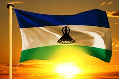 Drapeau du Lesotho tissant sur le beau coucher du soleil orange avec le fond de nuages illustration libre de droits
