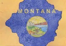 Drapeau du Montana d'état d'USA dans le grand trou criqué concret et le mur cassé image libre de droits