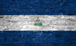 Drapeau du Nicaragua au-dessus d'un vieux fond de mur de briques, surface photo stock